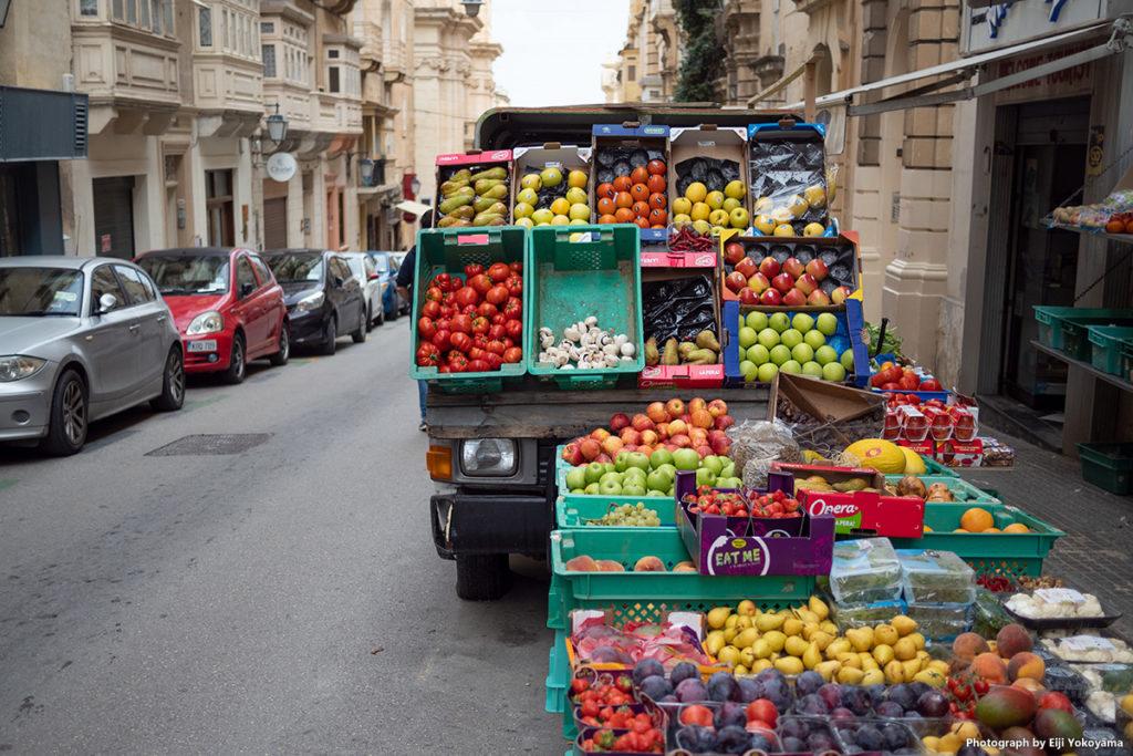 街の八百屋さん。店の前に車まで置いて野菜を並べています。